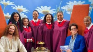 man gekleed als Jesus, naast gospelkoor gekleed met paars togas en presentator met donkere blauw jas