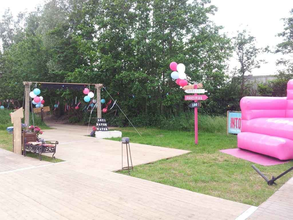 big pink blow up chair with ballons at a festival wedding
