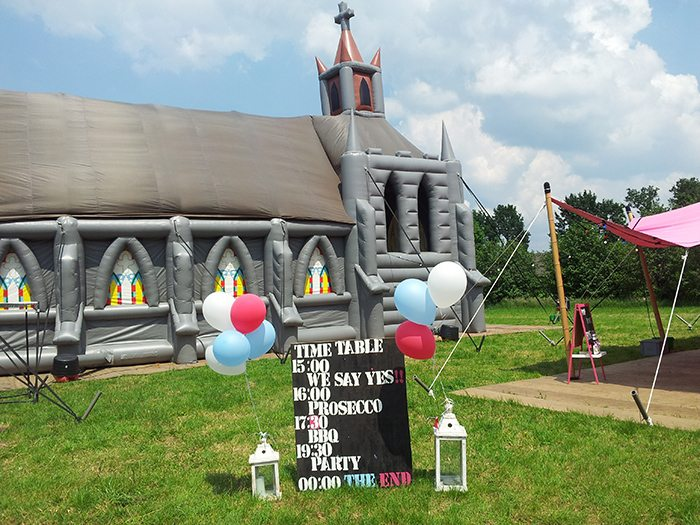 grey inflatable church on the grounds of a family farm