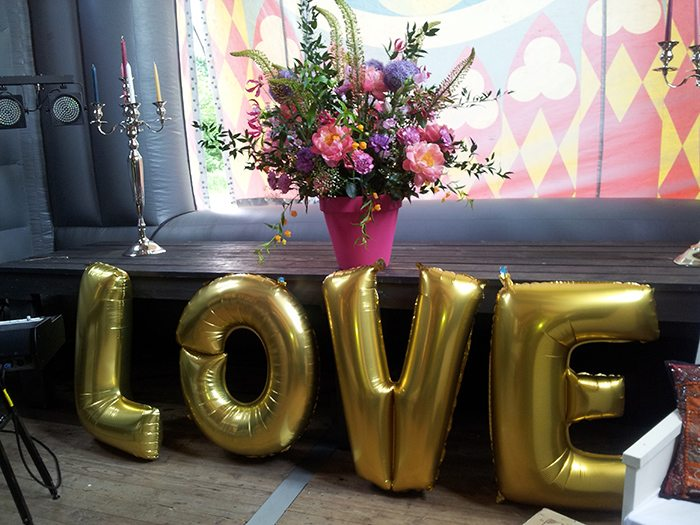 wedding decorations sign love, silver candle holders and colourful flowers