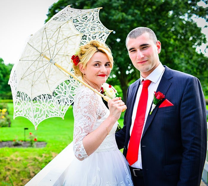 bride holding umbrella and posing with the groom in the park