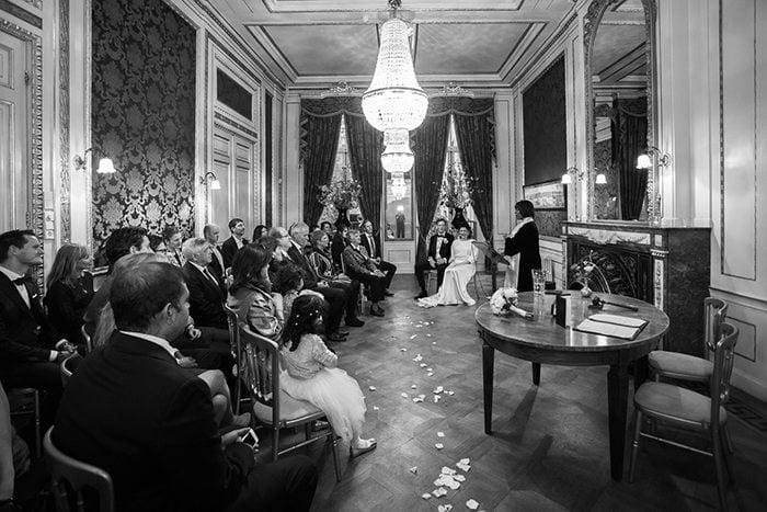Geregistreerd partnerschap vieren gasten zitten met ingehouden adem en grote ogen naar de ceremoniespreker te luisteren