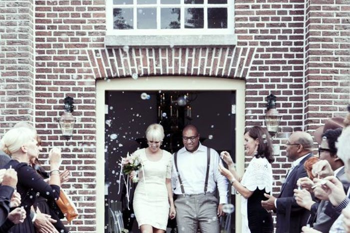 Happy couple leaving the church and guests congratulating them in an array of bubbles.