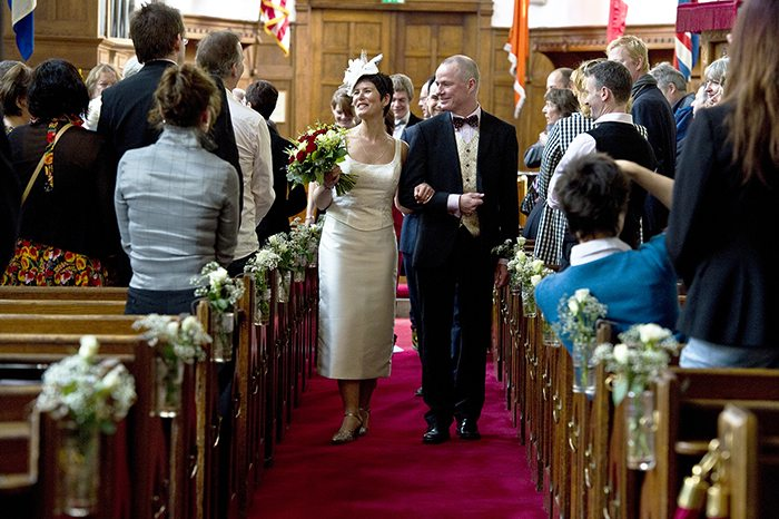 bride and groom walk up the church aisle after their marriage service