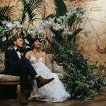 Eco-Friendly Wedding couple sitting in front of green plants embraced at the altar