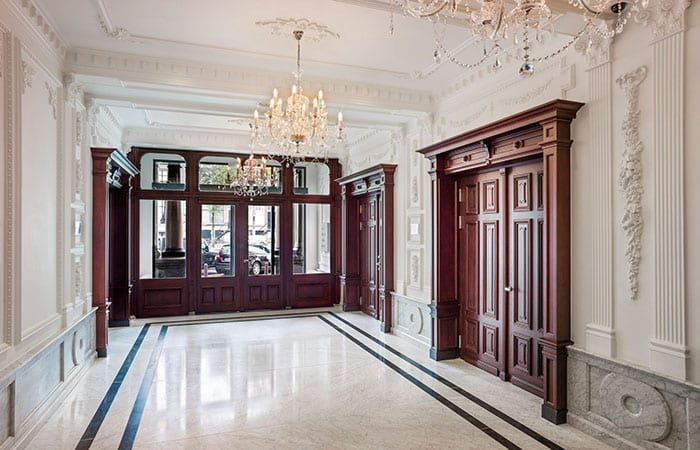 Thursday wedding Andaz Hotel Amsterdam marble entrance with decorative carvings on the walls and chandelier to hotel and exit to canals