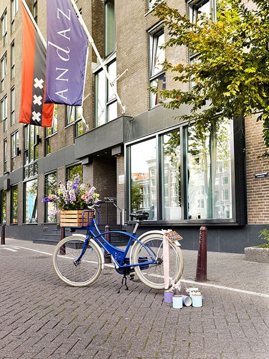midweek weddings Dutch blue bicycle with tin cans and multicoloured flowers in a wooden basket parked on the prinsengracht Amsterdam