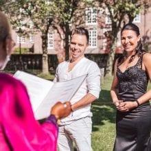 Elopement ceremony in NederlandStiekem trouwen vrouw met tattoos in een zwarte satijnen jurk en man in witte hemd en broek staan onder een boom