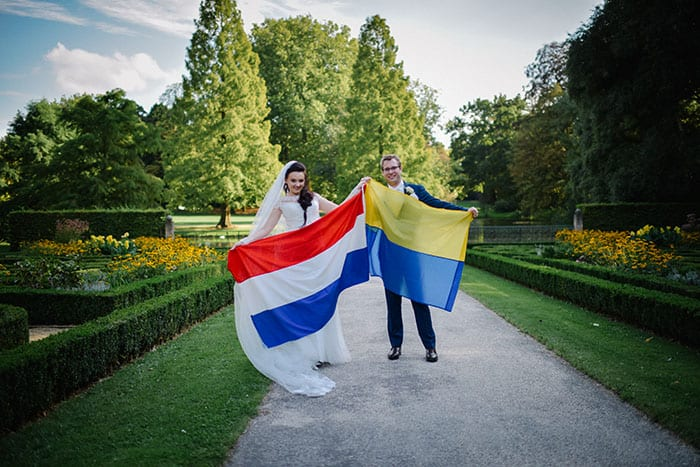 vondelpark wedding bride and groom holding a dutch and ukraine flag