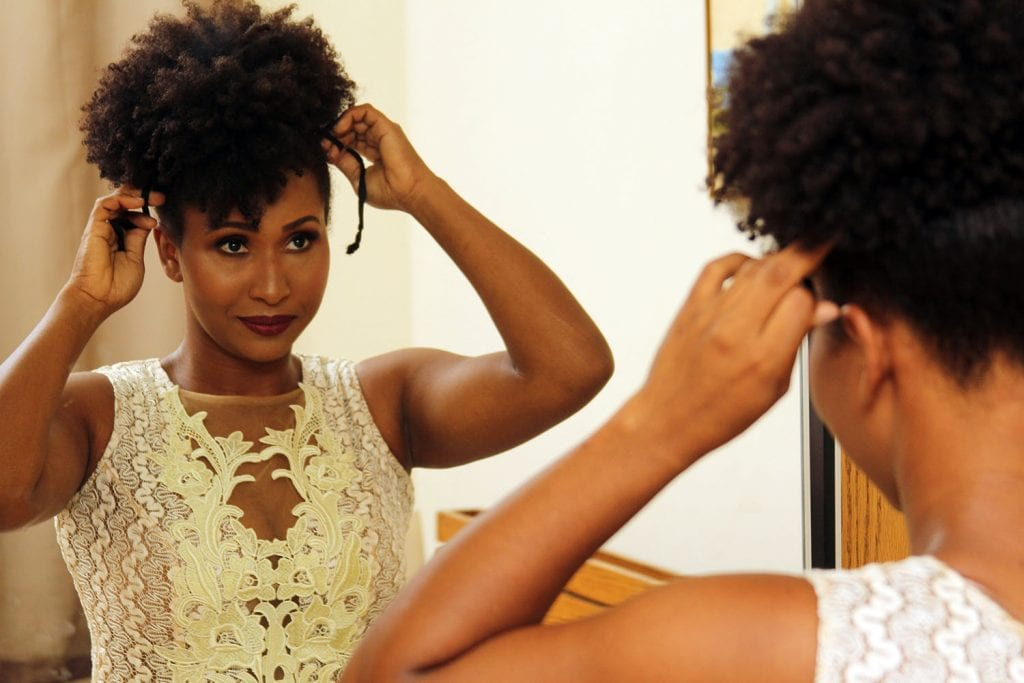 afro wedding hairstyles woman fixing her locks