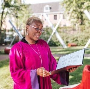 welcome woman wearing fuschia coloured gospel robe reading wedding speech