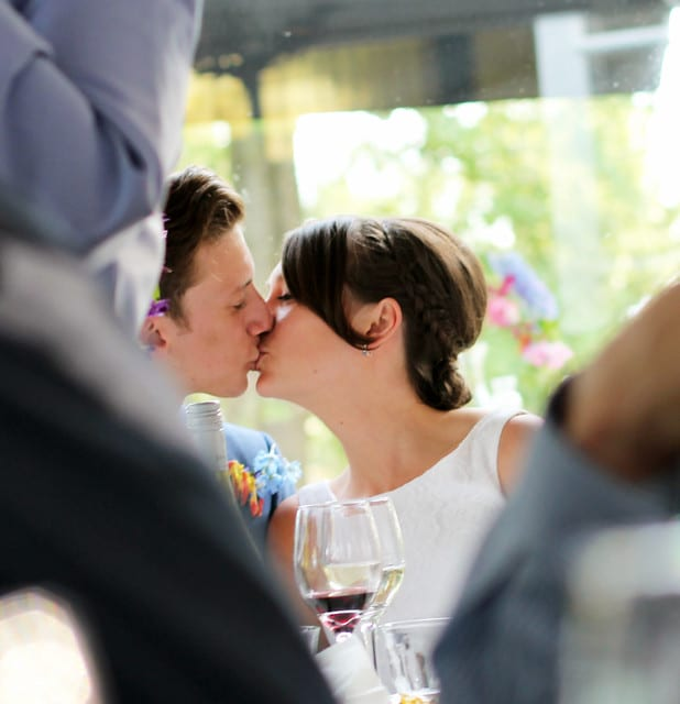 Waterside wedding  restaurants groom and bride kissing