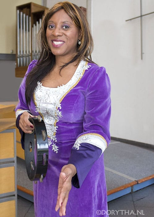 Rythm coaching woman wearing a purple and silver velour dress with a tamborine in her hand