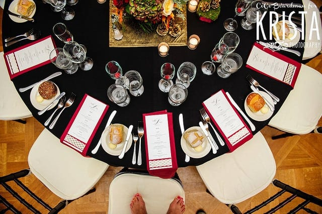 micro wedding celebration black round table with white chairs