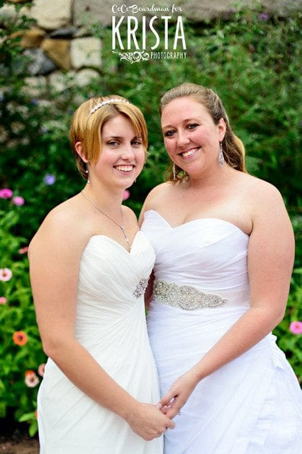 wedding ceremony readings two brides dressed in gowns holding hands