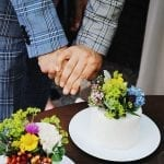 same-sex married couples two grooms dressed in grey checkered suits cutting wedding cake