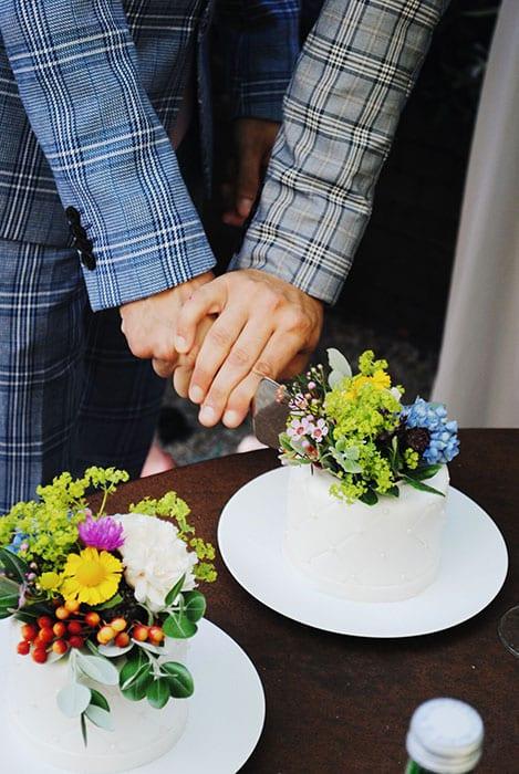 sprankelend trouwen op een doordeweekse dag bruidegommen gekleed in geruite grijze pakken snijden taart op receptie