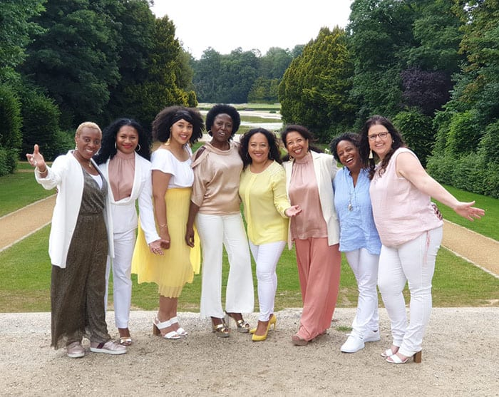 eight choir singers dressed in pastel rose, blue, white and yellow jackets, pants, skirts and blouses
