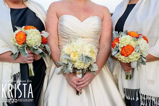 wedding dress code three women smartly dressed in blue and white satijn dresses holding orange bridal bouquets