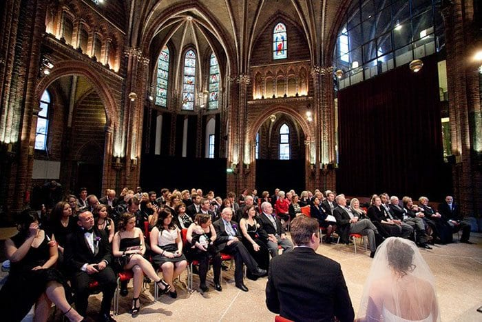 Amsterdam church wedding venues bride, groom and lots of family and friends listening to church service