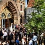 Amsterdam church wedding venues newlyweds leaving building and guests looking on