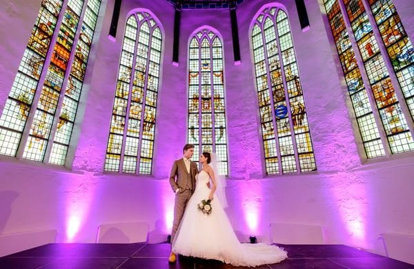 man and woman standing on an altar in front of a stained glass window
