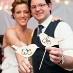 difficult wedding decisions couple holding wooden cut-outs of two love birds wit the words we do