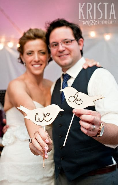 wedding planning checklist couple holding wooden cut-outs of two love birds wit the words we do