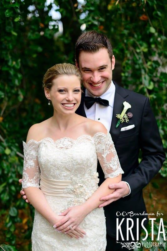 groom in tuxedo hugging bride in white dress
