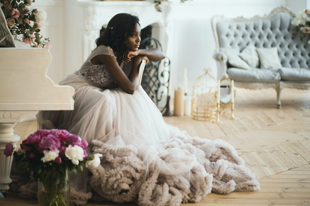 wedding day hair woman in white floral dress sitting on white chair