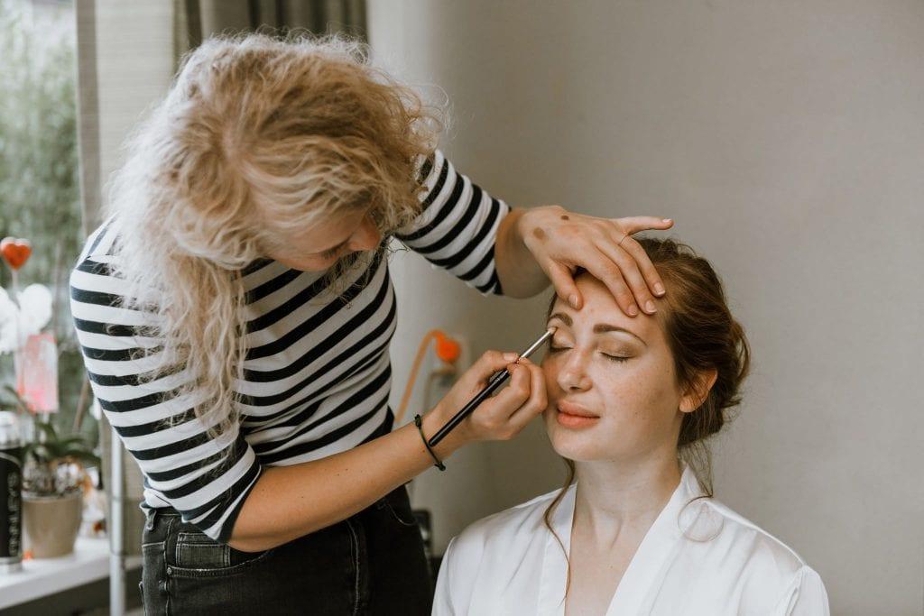 wedding day hair woman applying make-up on bride's eyes