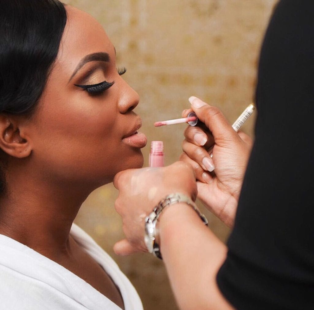 Afro wedding hairstyle black woman putting pink shiny gloss on woman of colour