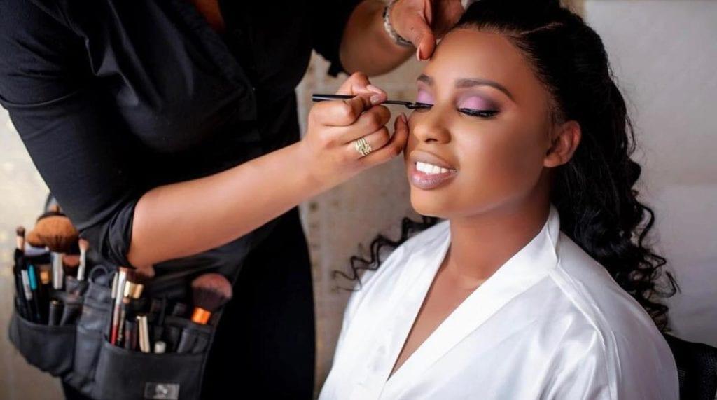 black woman applying purple eyeshadow on woman's face
