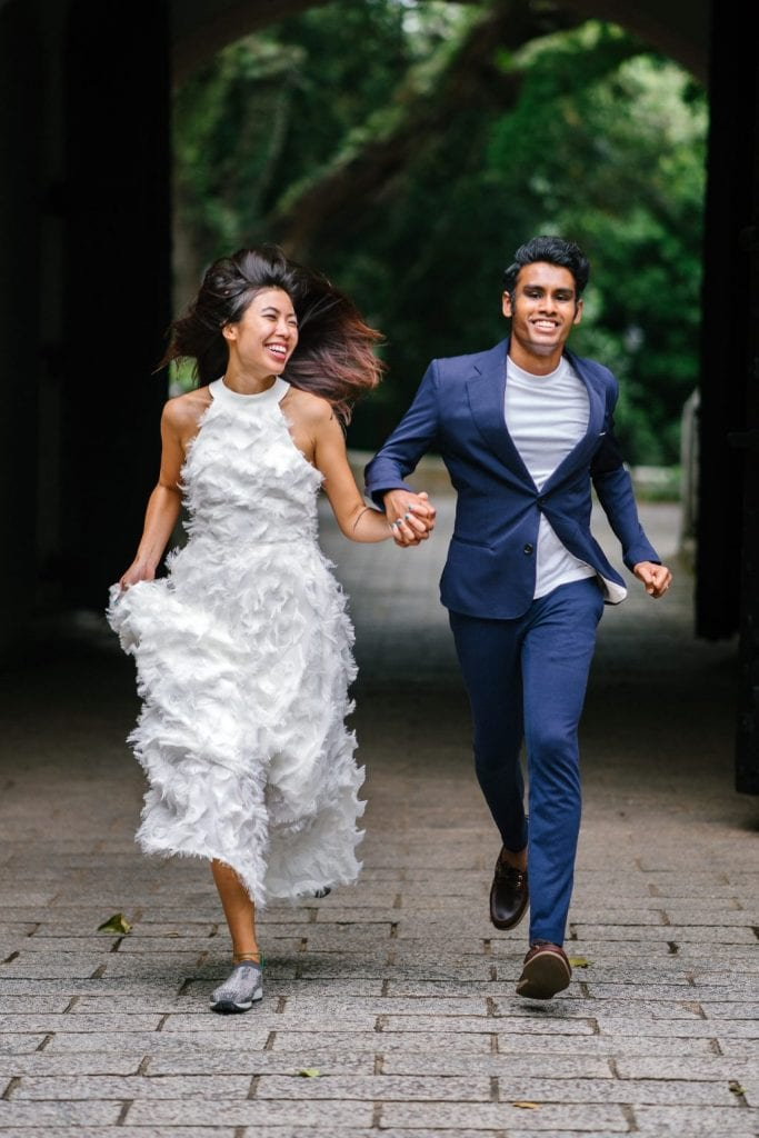 Budget bruiloft bride and groom holding hands and running
