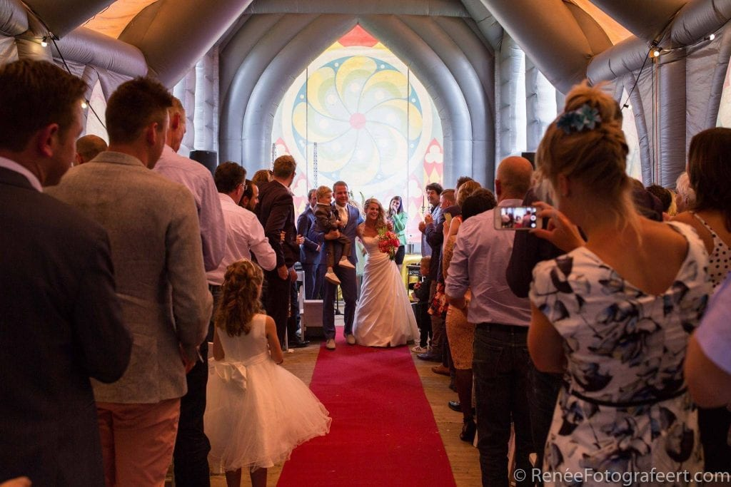 Alfresco wedding happy couple walking hand in hand up the red carpet runner