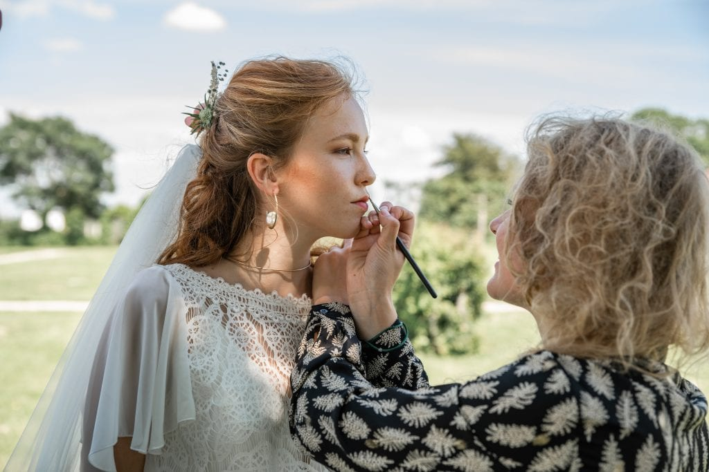 coronavirus weddings make-up artist putting lipstick on a bride