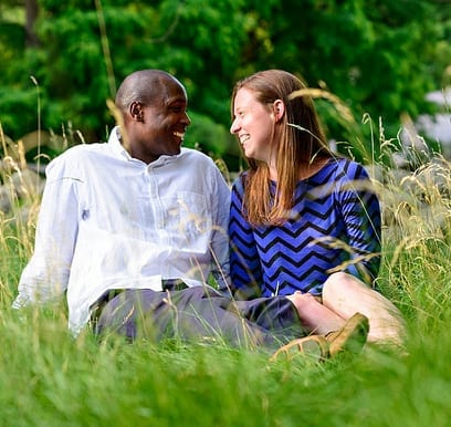 mixed-race marriage black african man sitting in the grass with white caucasian woman smiling at one another