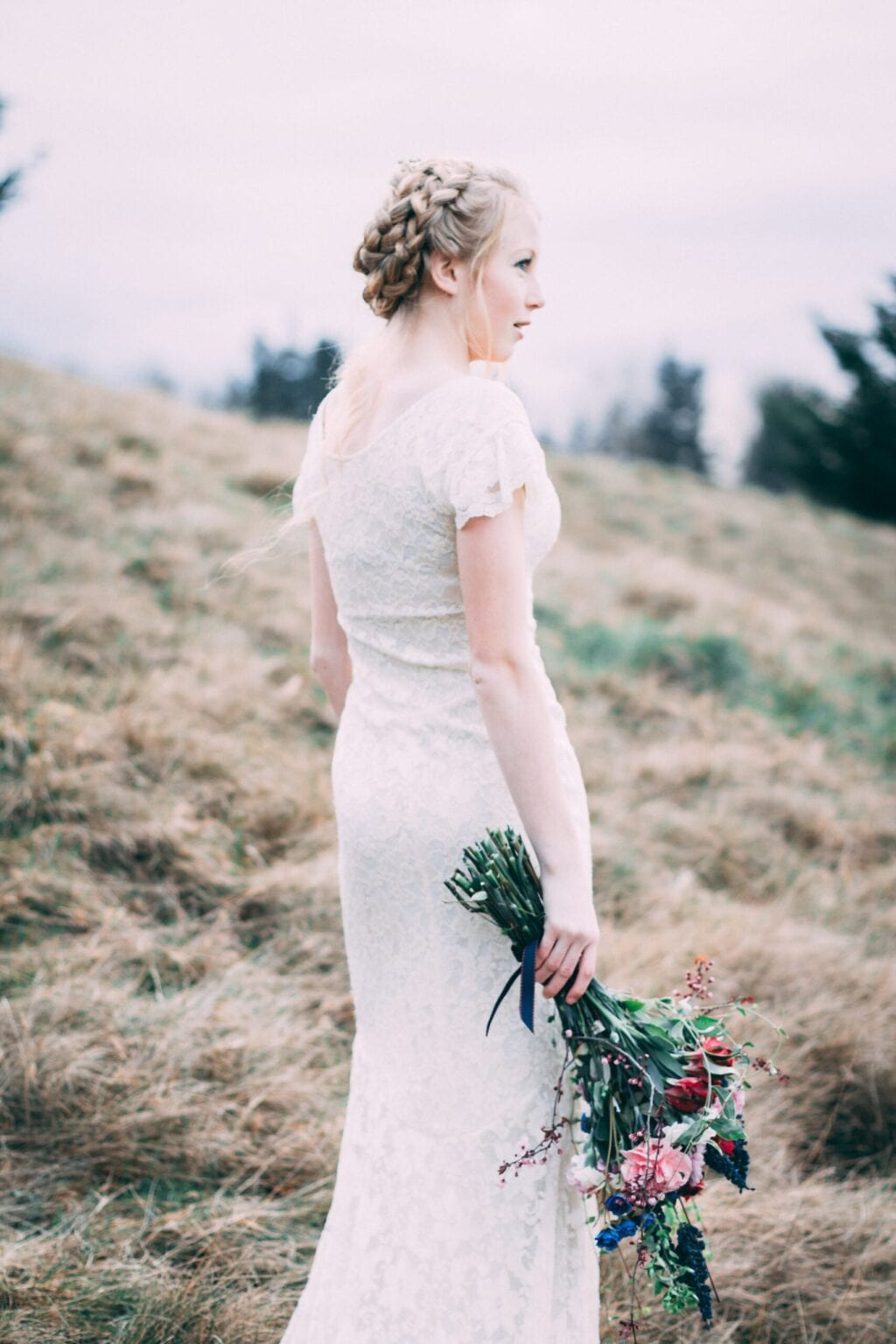 woman wearing a white laced bridal gown standing in a hayfield holding red, pink, blue flowes and green foliage
