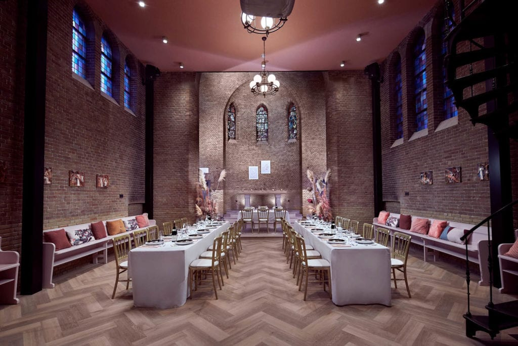 Dutch church wedding venues white tables with gold chairs set within a lighted chapel