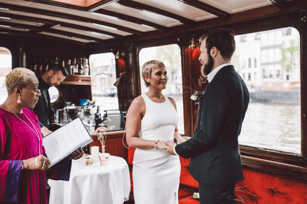Getting married aboard a boat in Amsterdam bride dressed in white dress with split and groom with dark grey suit and buttenhole
