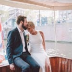 getting married aboard a beautiful boat in amsterdam couple sitting in the back of the boat kissing