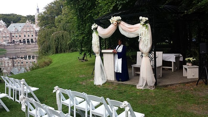 wedding officiant celebrant standing under the altar of love at a stately home in Holland