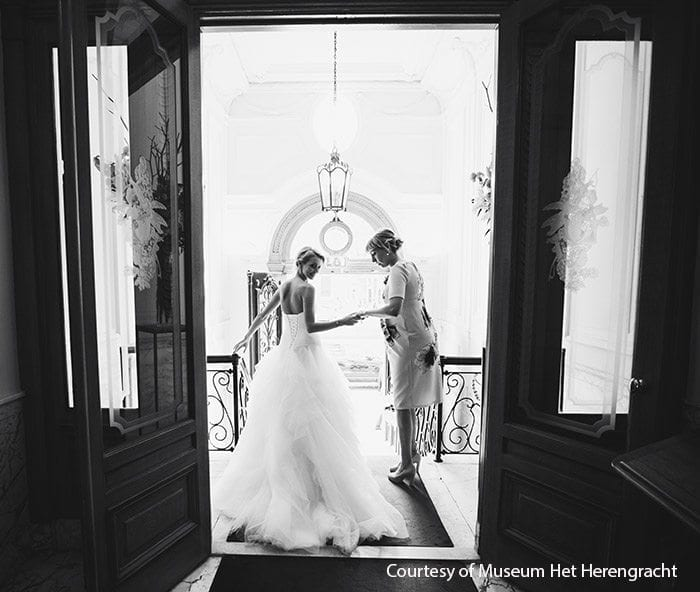 Geregistreerd partnerschap vieren bruid en ceremoniemeester staan op de traploper balustrade aan beide zijden