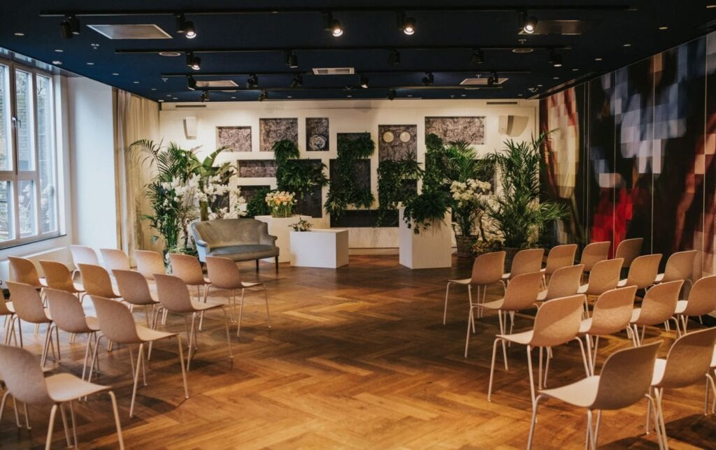 Midweek Weddings ceremony space with light grey love seat surrounded by green palm trees and facing white seating arrangement in Andaz Hotel Amsterdam