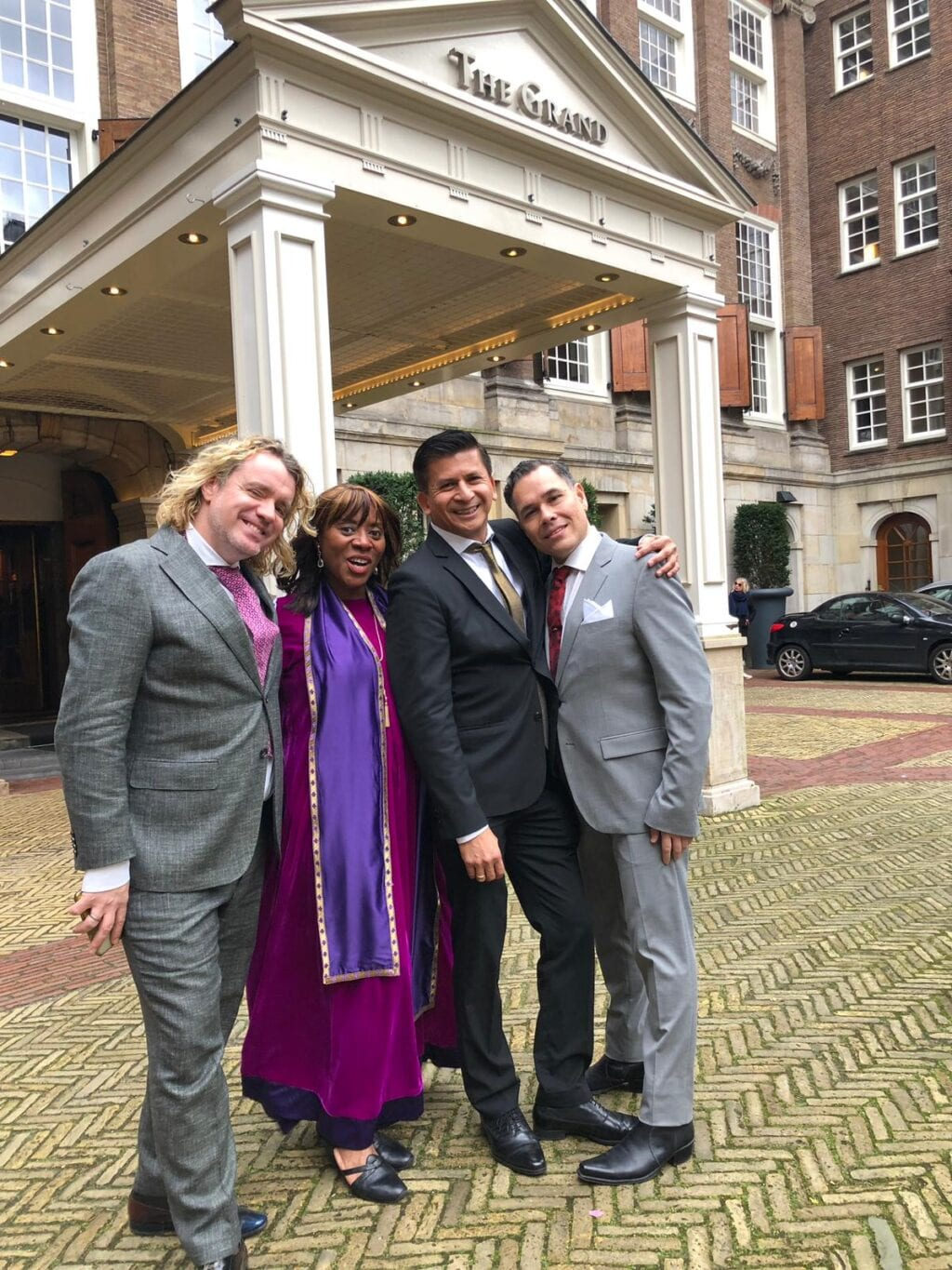 wedding reviews woman in purple robe with gay couple dressed in grey wedding suits