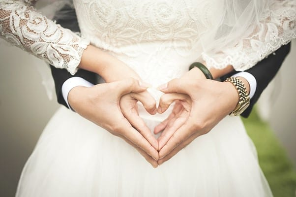man and woman embraced making a love symbol with their hands
