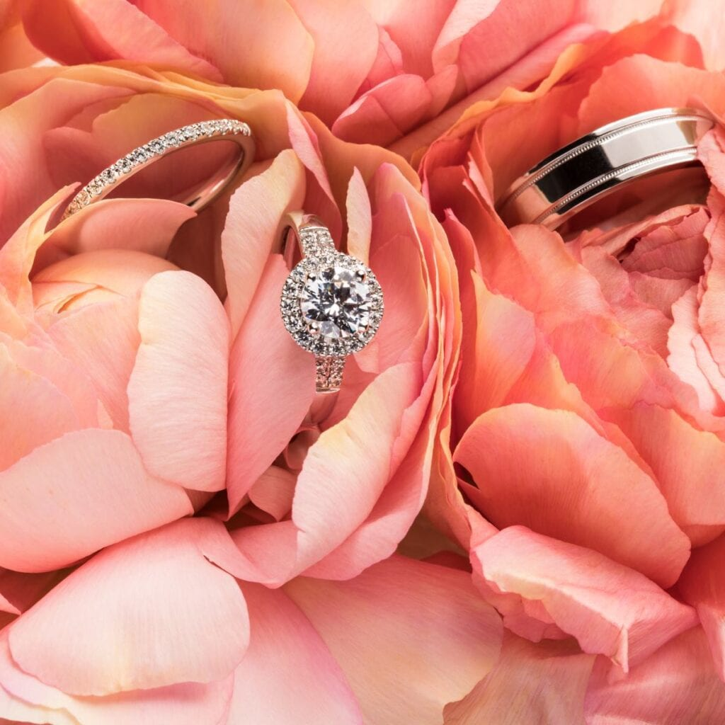 Pre-Wedding Interview Questions engagement ring and two wedding rings settled in a bed of pink roses
