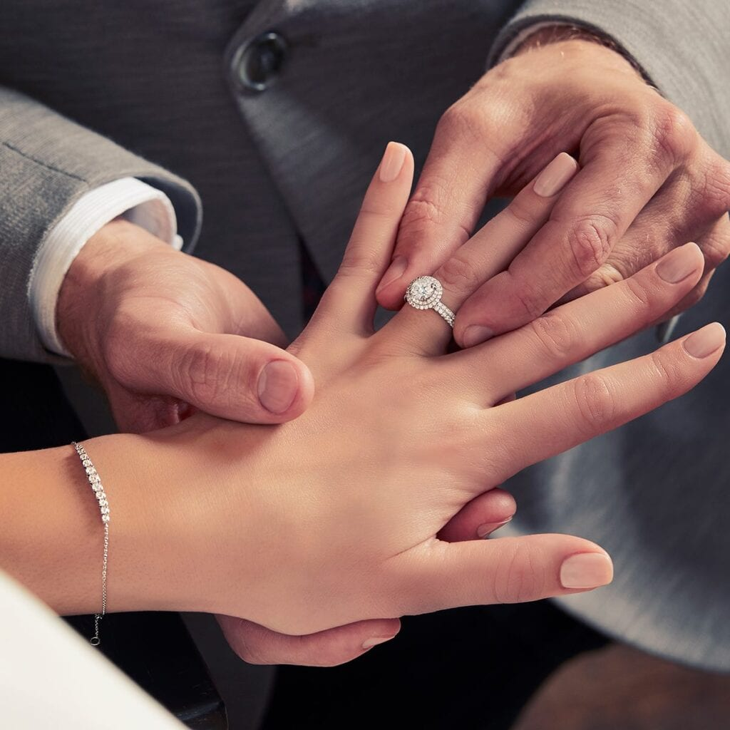 man in grey suit putting diamond engagement ring on woman's left hand finger