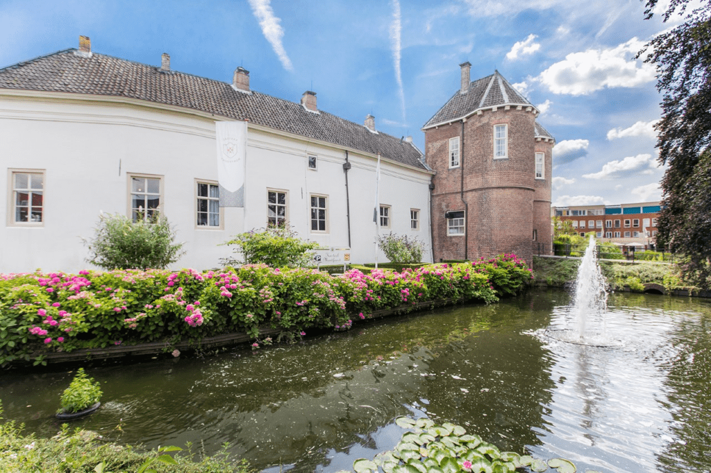 Dutch castle wedding venue fountain with moat and pink blooming flowers