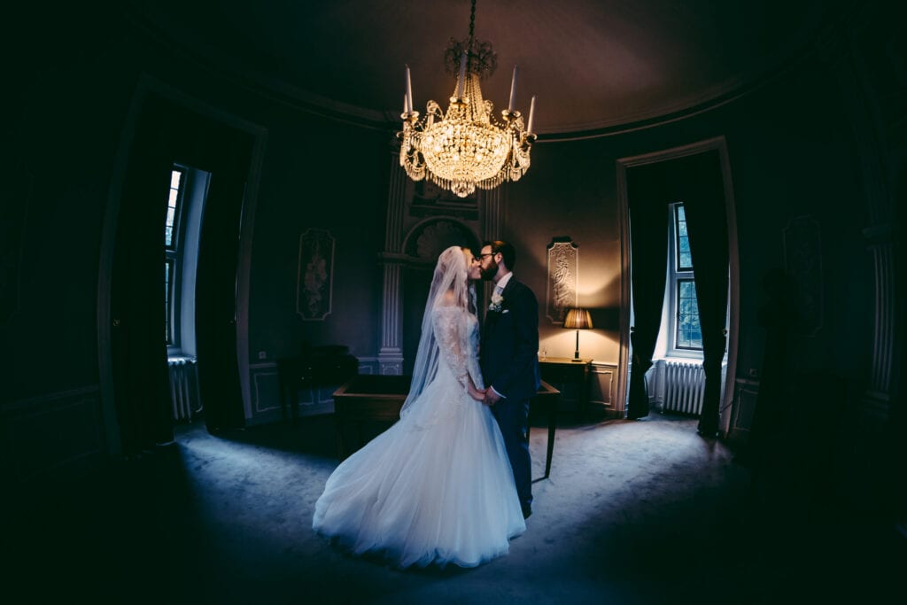 symboli wedding ceremony planning couple kissing under a crystal chandelier